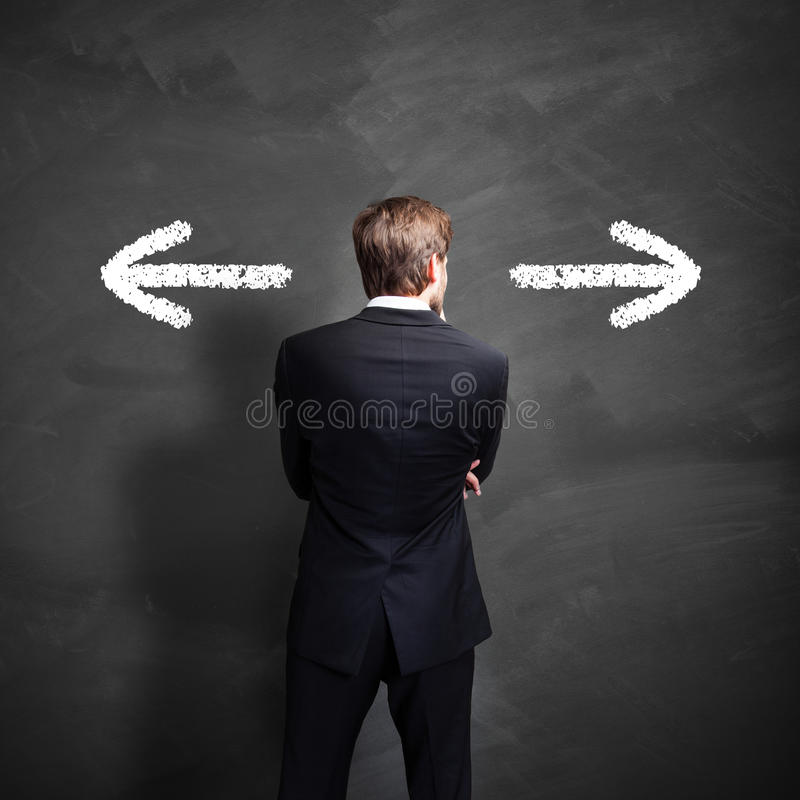 Businessman having to decide which way to go stock image