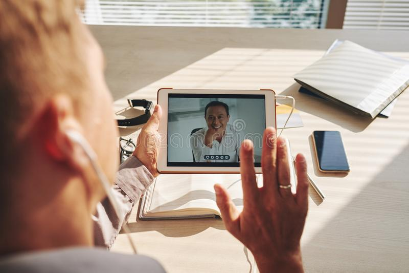 Video conference on tablet. Businessman having a video conference on tablet with his colleague at office stock photo
