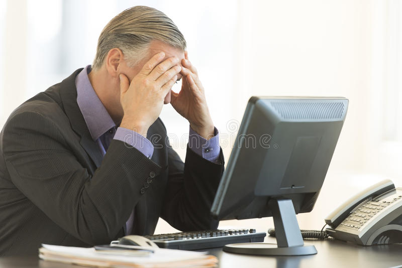 Download Businessman With Head In Hands Sitting At Desk Stock Photo - Image: 32430034
