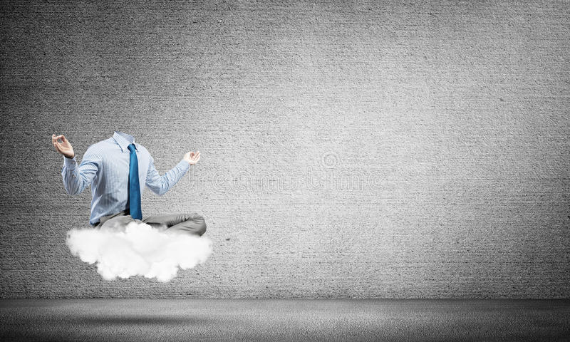 Businessman without head. Headless businessman sitting on cloud in lotus pose and meditating royalty free stock photos