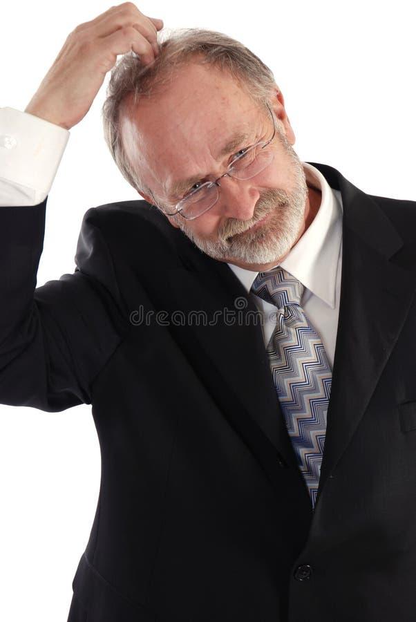 Businessman head scratch. Senior businessman scratching his head stock image