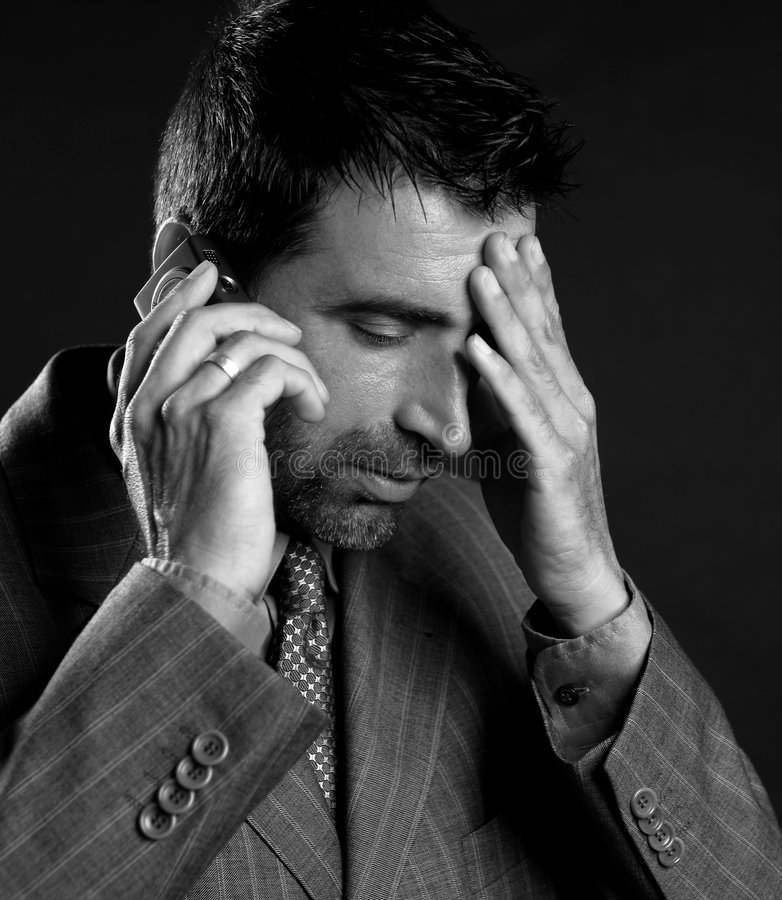 Businessman with headache and mobile phone stock photos