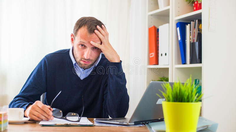 Businessman with headache sitting in his office. royalty free stock photography