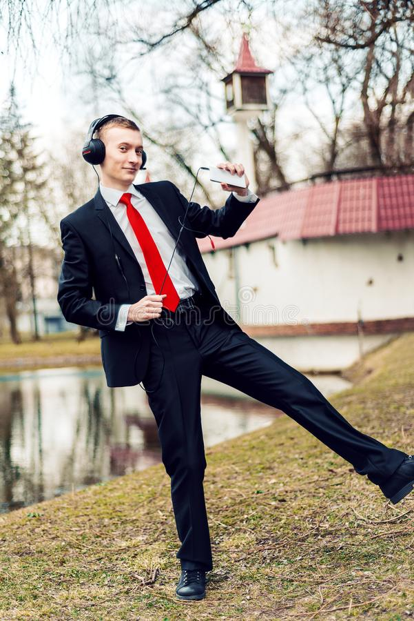 Businessman in headphones is dancing. the young man relaxes. freelancer resting royalty free stock photography