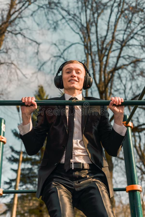Businessman in headphones pulls himself up on a sports horizontal bar. Modern young man. Startup business concept. royalty free stock images
