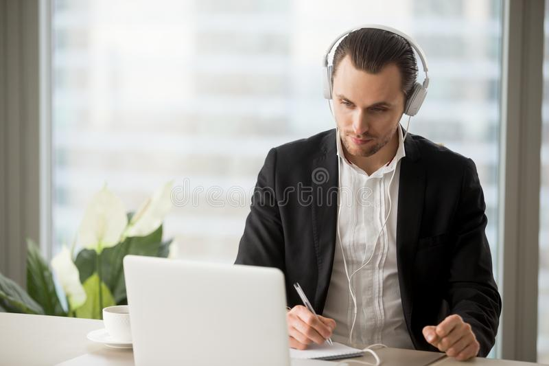 Businessman in headphones taking notes in front of laptop. royalty free stock image