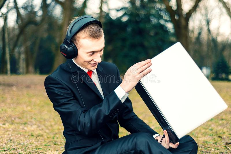 Businessman in headphones talking on the laptop. Internet communication. young guy in a suit on the nature. freelancer, distant stock image