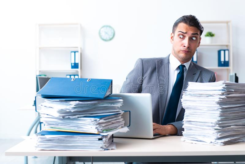 Businessman with heavy paperwork workload. The businessman with heavy paperwork workload stock images