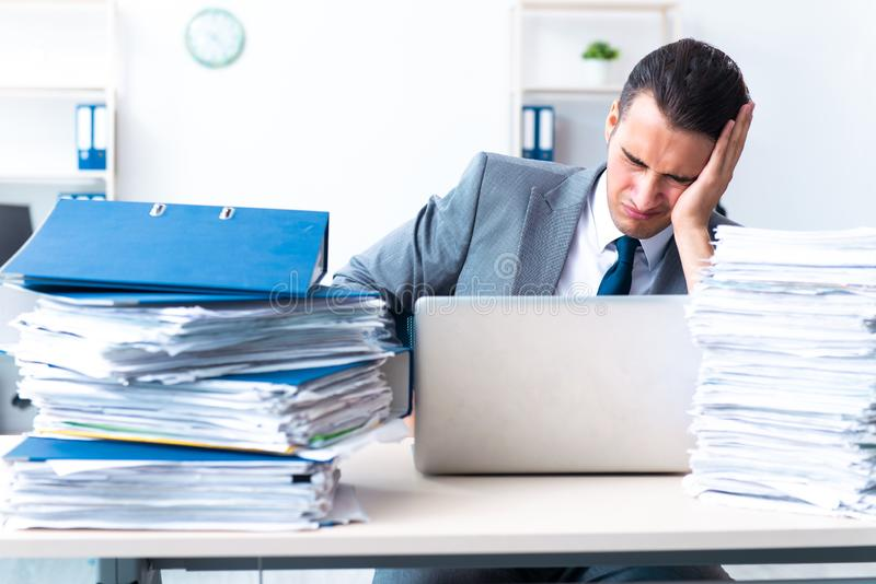Businessman with heavy paperwork workload. The businessman with heavy paperwork workload royalty free stock images