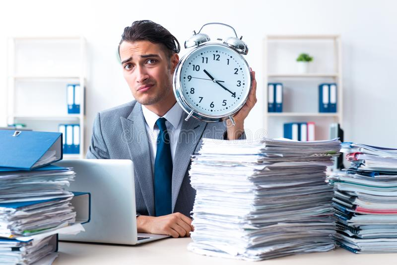 Businessman with heavy paperwork workload. The businessman with heavy paperwork workload stock photos