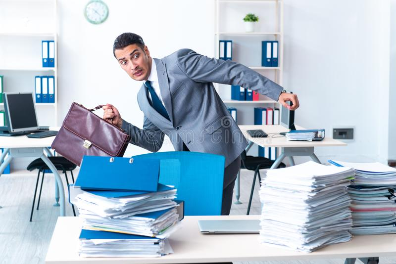 Businessman with heavy paperwork workload. The businessman with heavy paperwork workload royalty free stock photo
