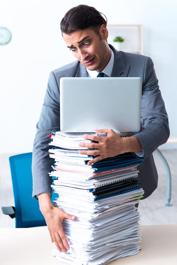 Businessman with heavy paperwork workload royalty free stock photo