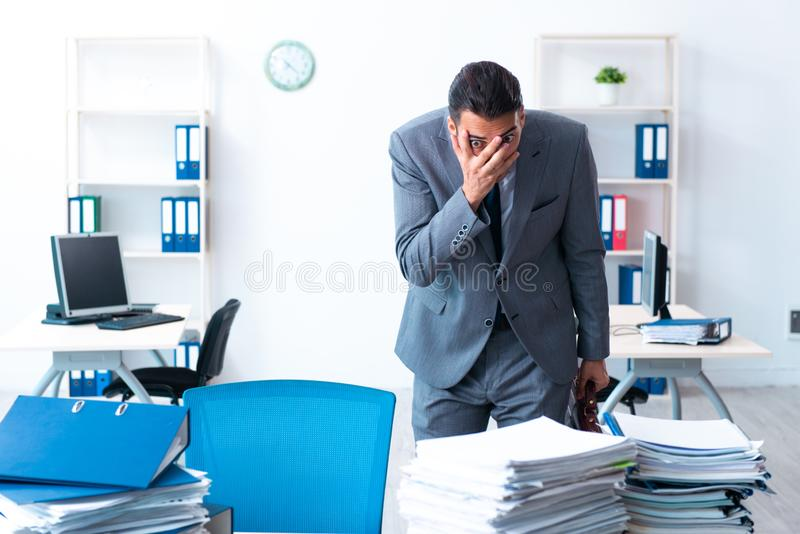 Businessman with heavy paperwork workload stock photo
