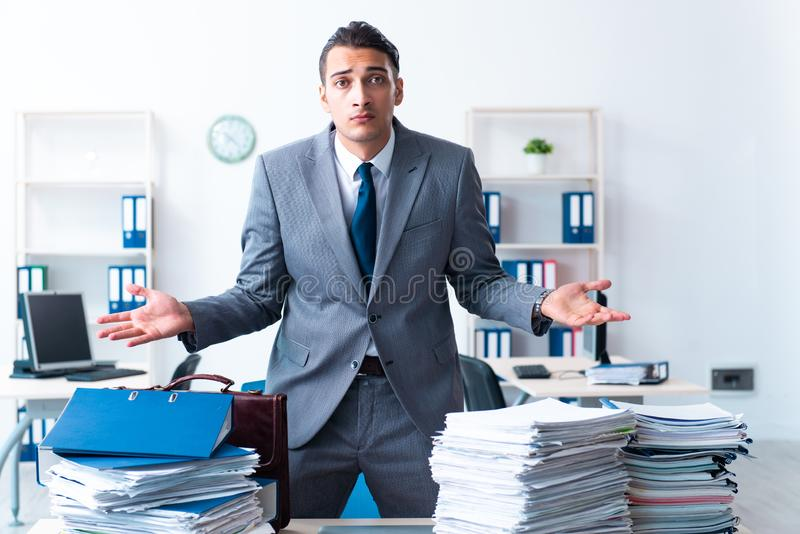 Businessman with heavy paperwork workload royalty free stock photography