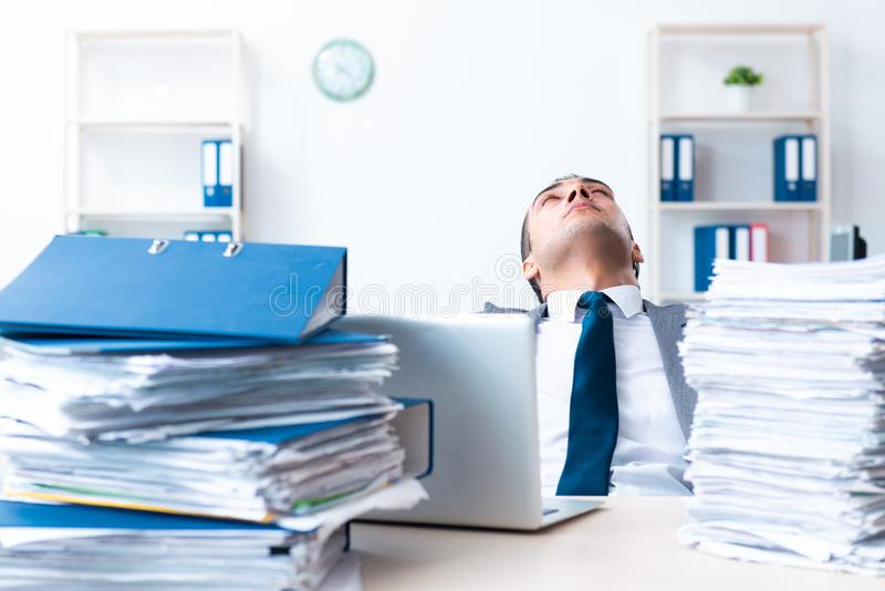 Businessman with heavy paperwork workload. The businessman with heavy paperwork workload stock photo