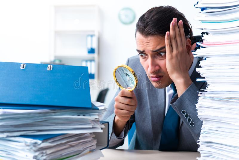 Businessman with heavy paperwork workload stock photography