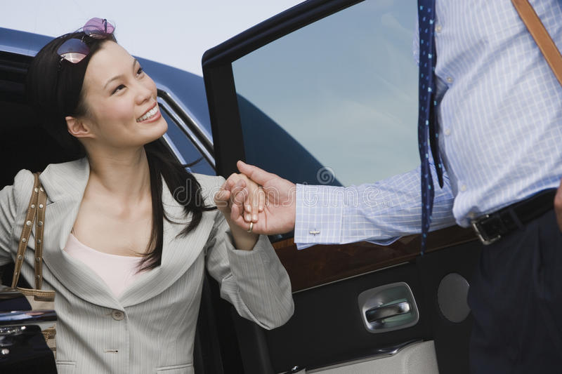 Download Businessman Helping Businesswoman To Get Down By Car Stock Image - Image of executive, person: 29653097
