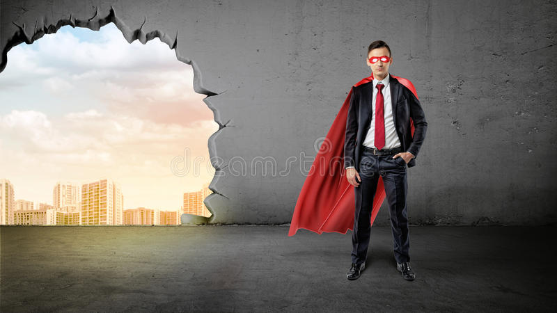 A businessman in a hero red cape with a hand in his pocket on concrete background with a hole to the city view. Business and success. Personal qualities royalty free stock images