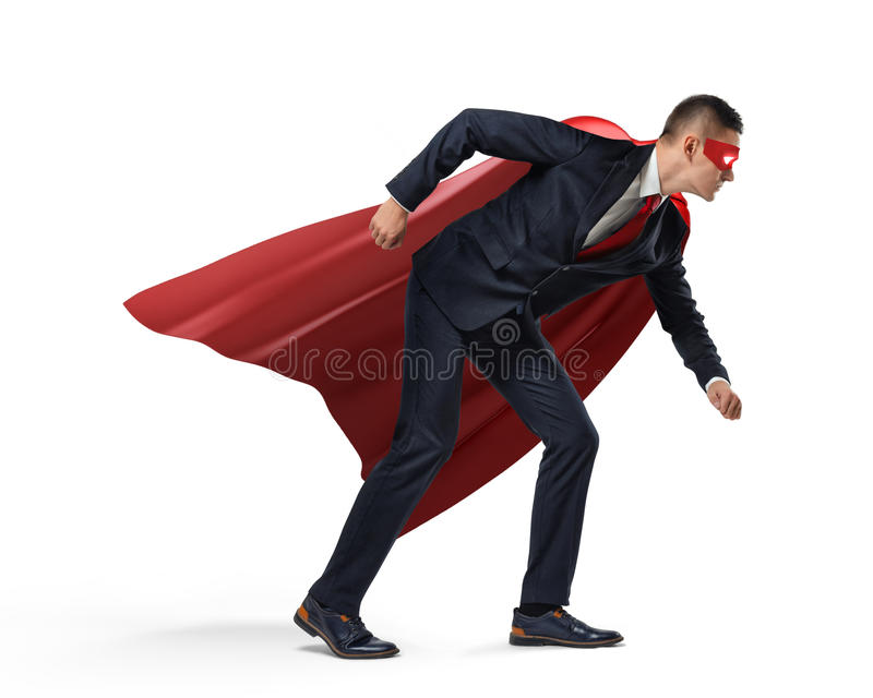 A businessman in a hero red cape and a mask standing in a side view in a starting line position on white background. Fighting competition. Fight for success royalty free stock photos