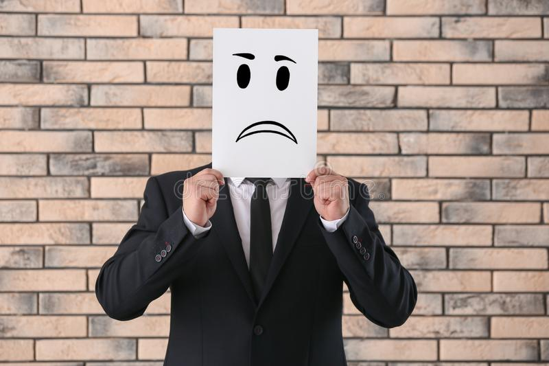 Businessman hiding face behind sheet of paper with drawn emoticon against brick wall royalty free stock images