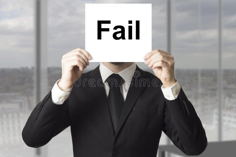 Businessman hiding face behind sign fail. Businessman in black suit hiding face behind sign fail royalty free stock photos