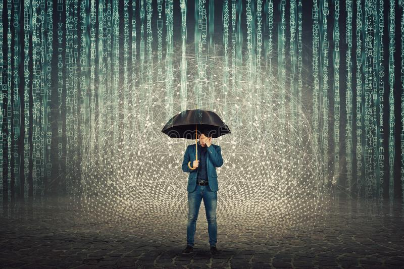 Businessman hiding face standing under umbrella shield to protect of internet viruses as matrix code numbers falling above like a stock image
