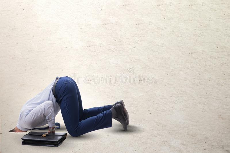 The businessman hiding his head in sand escaping from problems stock images