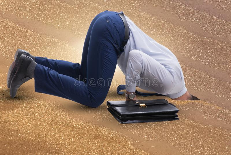 Businessman hiding his head in sand escaping from problems stock photos