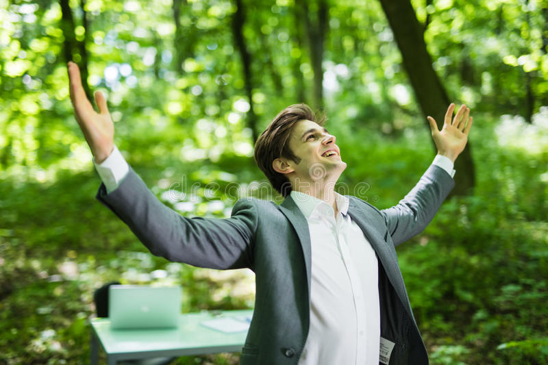 Businessman with his arms wide open in green park in front of his office. Business concept stock photography