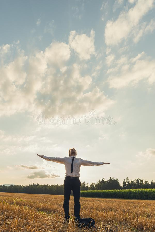 Businessman with his arms wide open standing under cloudy evening sky stock image