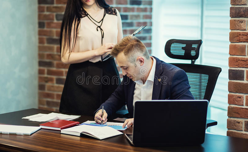 Businessman and his assistant Secretary in his office. The Secretary brought the boss documents to sign,Boss signs the documents royalty free stock photography