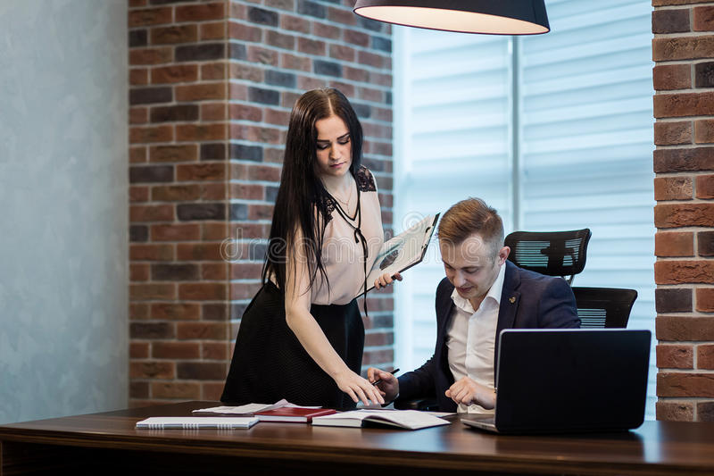 Businessman and his assistant Secretary in his office. The Secretary brought the boss documents to sign,Boss signs the documents. Brought by the secretary stock photos