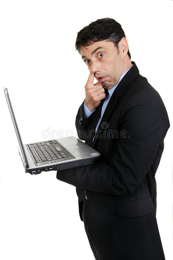 Businessman with his finger to his. Middle-aged businessman standing sideways handholding his laptop computer gesturing with his finger to his nose in rude stock photography