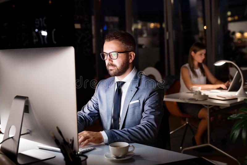 Businessman in his office at night working late. stock photos