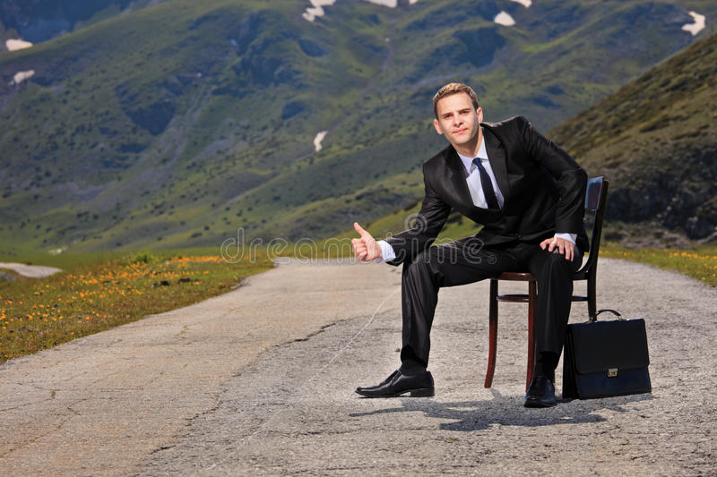 Businessman hitchhiking. On a highway royalty free stock photography