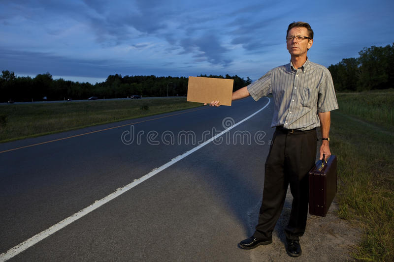 Businessman hitchhiking to work. With a blank sign stock image