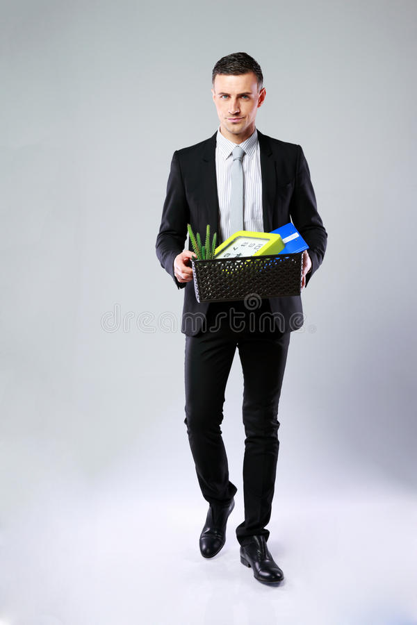 Businessman hold box with personal belongings. On gray background stock image
