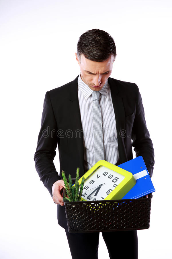 Businessman hold box with personal belongings. You are fired! Businessman hold box with personal belongings on gray background royalty free stock image