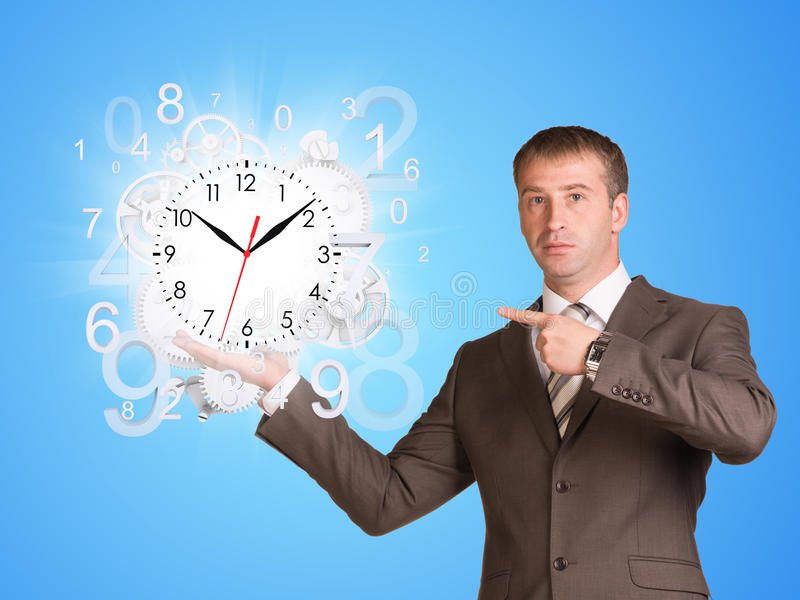 Businessman hold clock with flying figures stock image