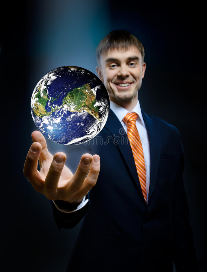Businessman. Hold in hand terrestrial globe, on dark blue background, business concept image planet by: Stokli, Nelson, Hasler Laboratory for Atmospheres stock image