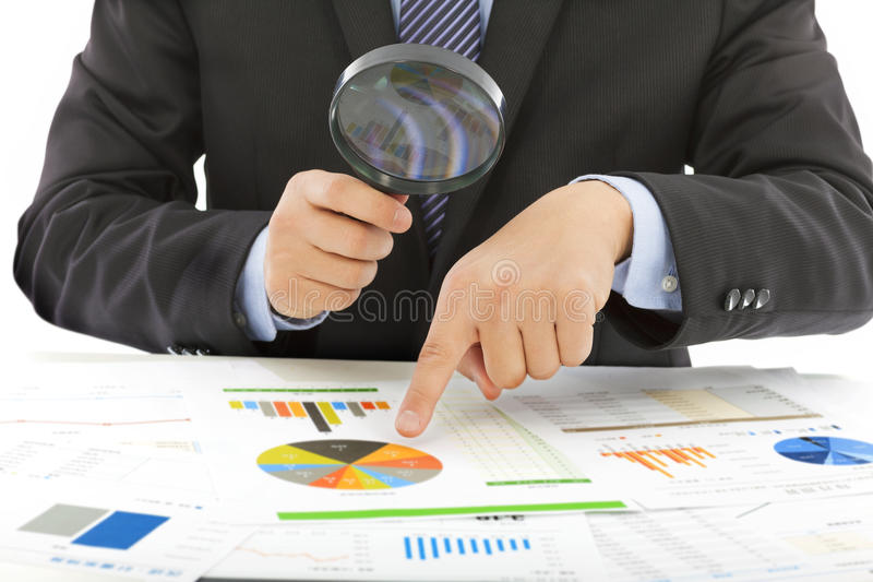 Businessman hold a magnifying glass to check stock image