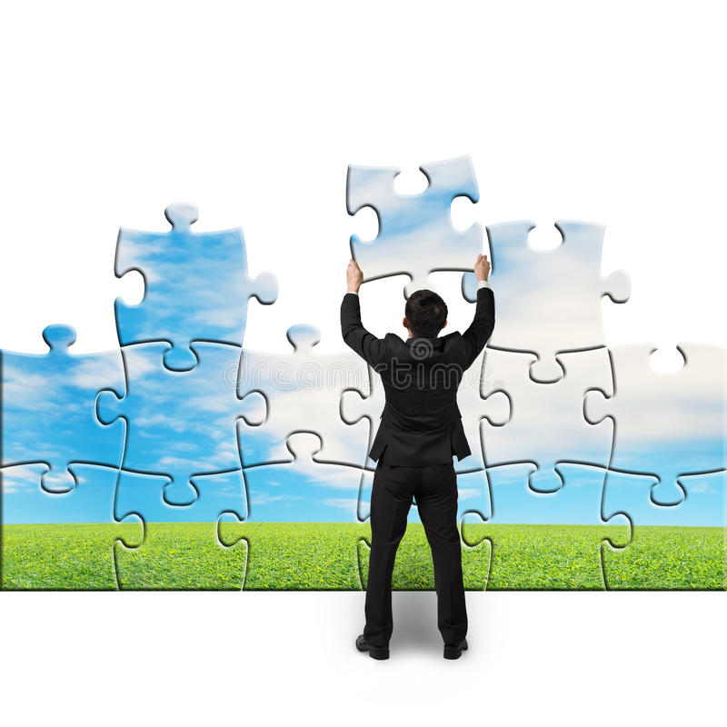 Businessman hold puzzles to assembly. In white background royalty free stock image