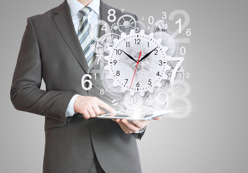 Businessman hold tablet pc with clock and gears. Gray background royalty free stock photo