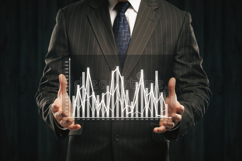 Businessman holding abstract business graph. On dark background background royalty free stock photo