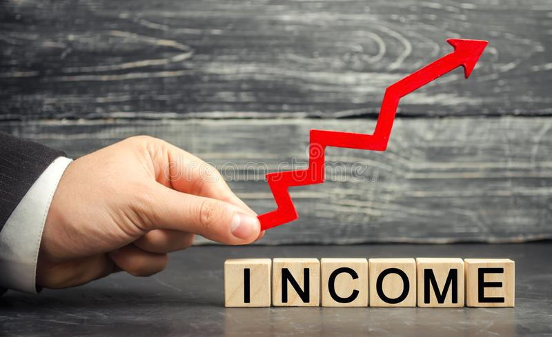 A businessman is holding an arrow up above the inscription Income. Concept of business success, financial growth and wealth. Incre. Ase profits and investment royalty free stock photos