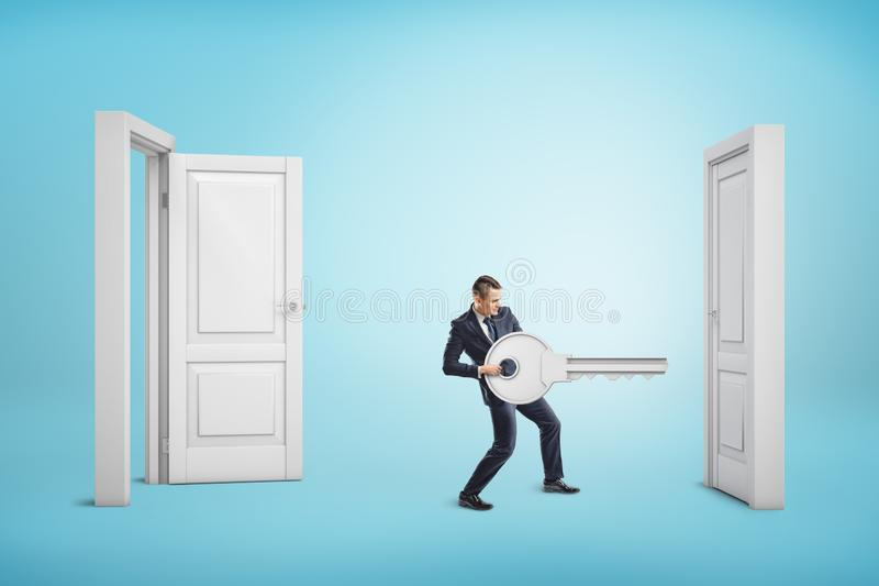 Businessman holding big key between an open door and a closed one on blue background stock photos