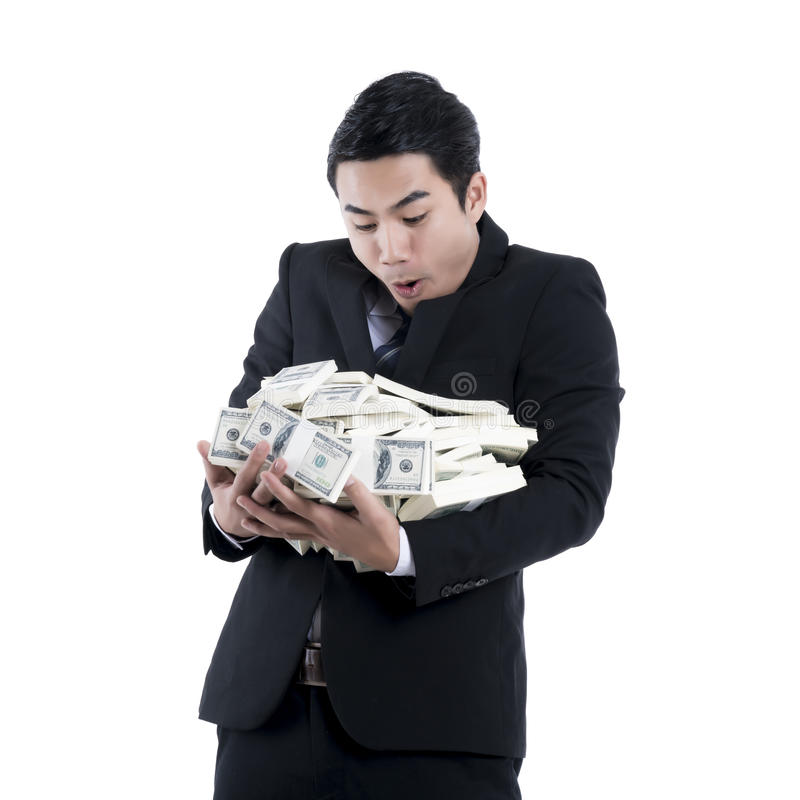 Businessman holding a big pile of money in his arms on white background stock photos