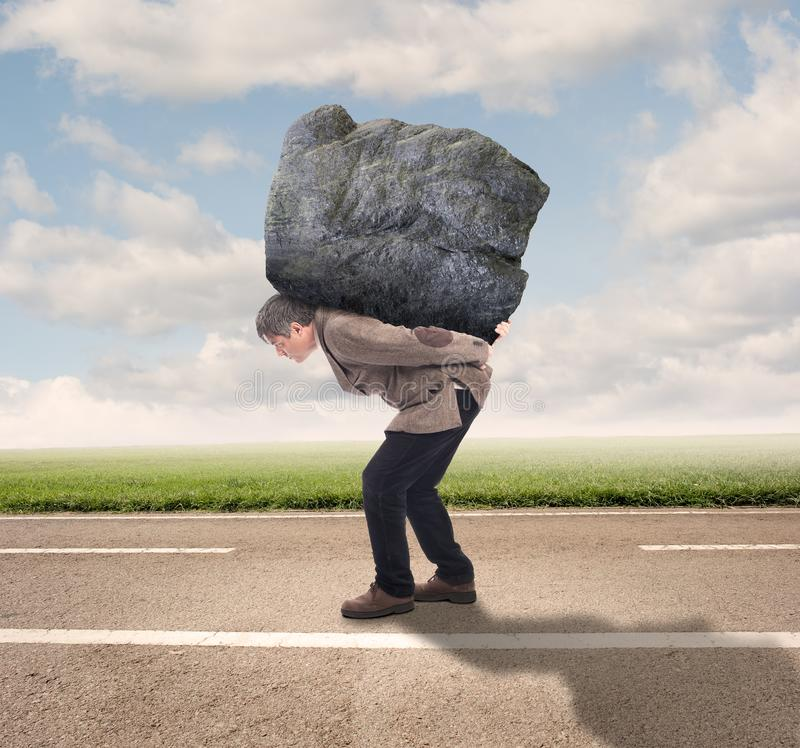 Businessman holding a big rock. On a road royalty free stock photo