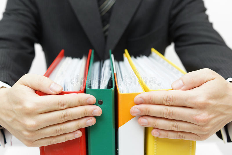 Businessman holding binders at office royalty free stock photography