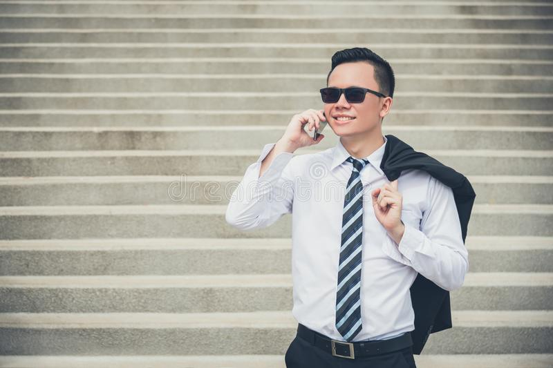 Businessman holding black suit talking with someone via mobile phone royalty free stock photo